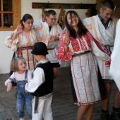 Girls in traditional dress dance with visitors from Germany